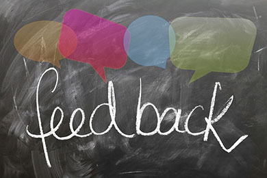 "The word ""feedback"" appears handwritten on a chalkboard with multi-colored thought bubbles above it."